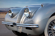 Close Up profile of nose of a silver 1954 Jaguar xk 120. photographed in the Desert of Palm Springs, CA