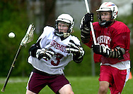A Portsmouth High School attackman drops his stick after a check by a Trinity player during the game in Portsmouth, NH.