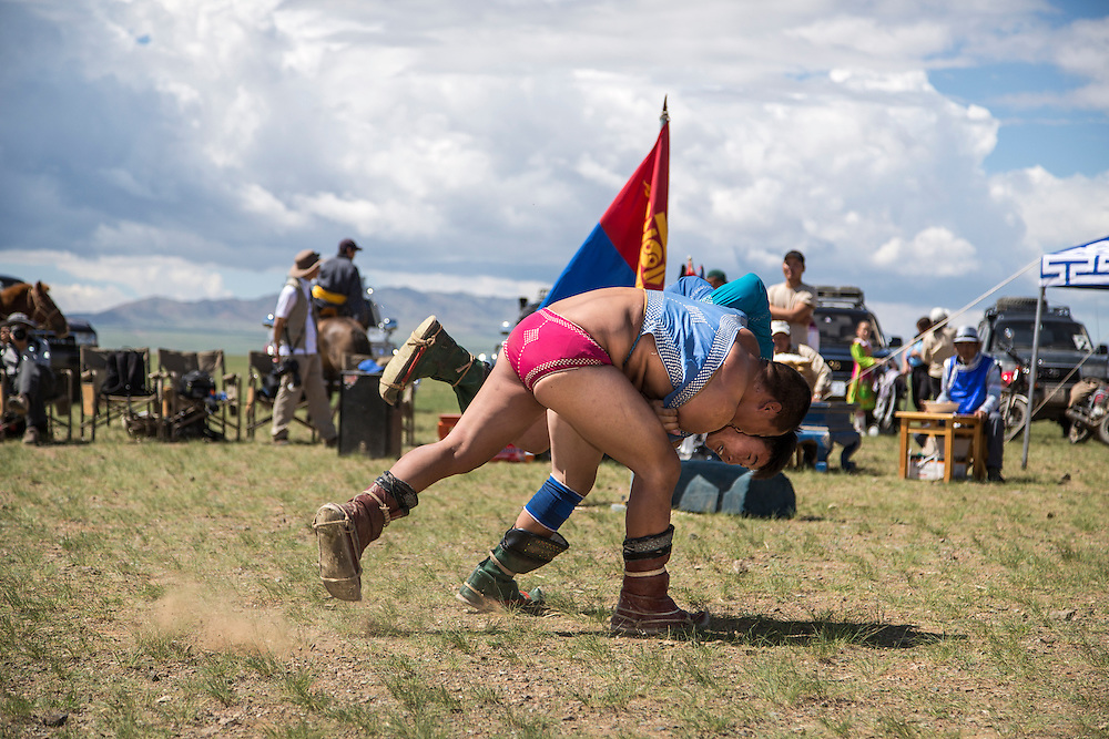 Two men compete during the first round of the wrestling competition of the Naadam Festival at the Three Camel Lodge in the Gobi Desert of Mongolia on July 31, 2012. Wrestling is one of the ?Three Manly Sports? practiced during the Naadam Festival. © 2012 Tom Turner Photography.