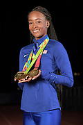 Dalilah Muhammad (USA) poses with 2019 IAAF World Athletics Championships in the women's 400m hurdles and 4 x 400m relay and 2016 Rio Olympics gold medal in the 400m hurdles, Monday, Dec. 16, 2019, in Lake Balboa, Calif. Muhammad, the world record holder in the 400m hurdles at 52.16 seconds. is only the second female 400-meter hurdler in history, after Sally Gunnell, to have won the Olympic and World titles and broken the world record.