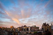 Balcony view of a New York City neighborhood with a colorful morning sky.