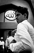 A muslim boy standing at the entrace to a mosque, UK, 2000's