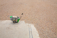 Street sweeper's cart on beach with tide advancing