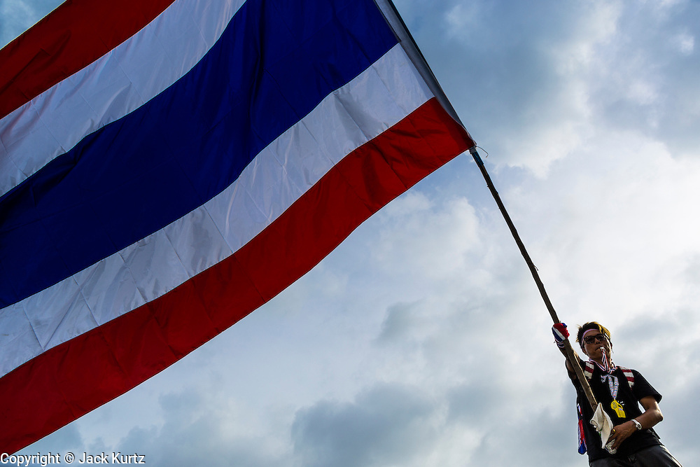 24 NOVEMBER 2013 - BANGKOK, THAILAND:     A Thai anti-government protestor waves a Thai flag during a protest on Rathcdamnoen Ave in Bangkok. More than 400,000 people packed onto Ratchdamnoen Ave in Bangkok Sunday, continuing an anti-government protest that started weeks ago over a blanket amnesty bill passed by the Thai Parliament. The amnesty bill was defeated in the Thai Senate and the protest morphed into a general protest against the government. The protestors are allied with the Thai Democrat party, the opposition party in parliament. Tens of thousands of pro-government Red Shirts have come to Bangkok to defend the government and are rallying in a different part of the city. Police have warned of clashes between the two groups but as of Sunday evening no problems had been reported. The protestors allege that the amnesty would allow fugitive former Prime Minister Thaksin Shinawatra to return to Thailand.        PHOTO BY JACK KURTZ