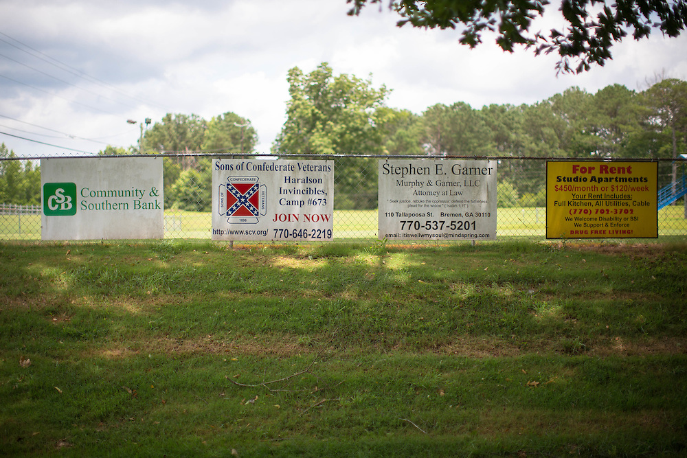An ad for the Sons of the Confederate Veterans sits among other signs at an athletics field at Haralson County High School on Thursday, July 2, 2015. Shot for a story about changes occurring in the South following a heightened national awareness and sensitivity concerning the Confederate battle flag. Photo by Kevin Liles for The New York Times