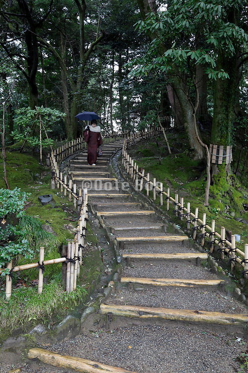 Japanese traditional dressed woman holding an umbrella coming down stairs in the Kenrokuen garden at Kanazawa Japan