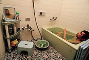 Kazuo Ukita relaxes in an ofuro (a Japanese bath that is meant for relaxation rather than washing). The water is generally kept in the tub and warmed before each use. Family members wash squatting on a stool with a bucket of hot water and a shower hose before entering the bath. When not in use the bath is covered with an insulated cover (seen behind Kazuo Ukita's head.) Japan. Material World Project. The Ukita family lives in a 1421 square foot wooden frame house in a suburb northwest of Tokyo called Kodaira City.