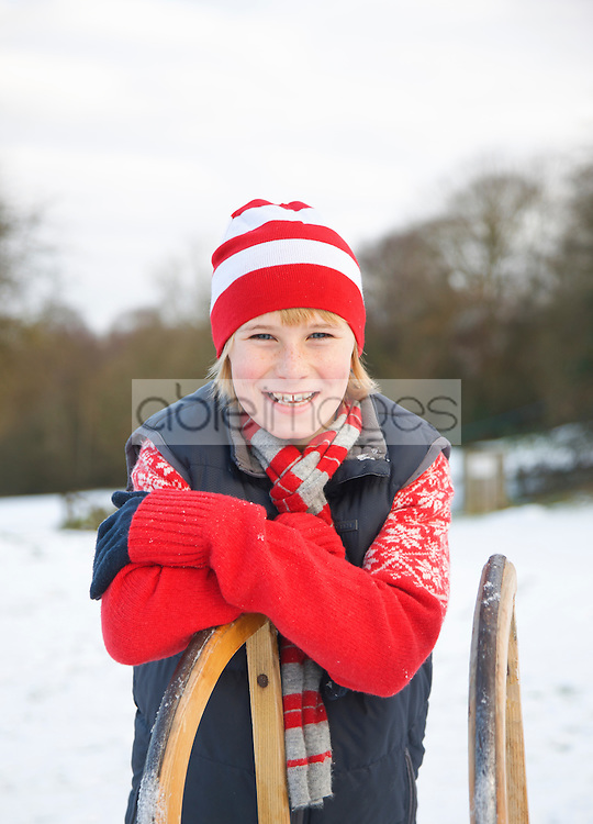 Portrait of a boy leaning on a sled