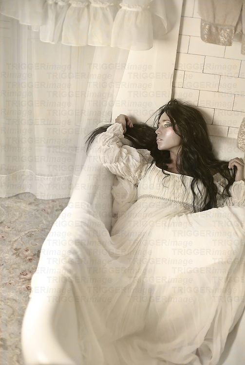 A dark haired woman in a long flowing dress lays in a bathtub, looking to the side. An all white tile background is behind her.