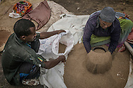 Vendor measures the indigenous Ethiopian grain, &quot;teff&quot;, into a coffee can, the standard method of measurement.  This poppy-seed sized grain is the staple cereal grain of Ethiopia.  It has been touted as the next super grain, being gluton-free, but Ethiopians have bigger worries, like whether the rain cycle will allow farmers to raise enough teff to avoid famine.  The main market in Lalibela in the Ethiopian Highlands.<br /> <br /> After the worst drought in decades, now experts worry that there is too much rain.  Neither extreme is ideal for teff cultivation.  For that reason aid groups like USAID have been distributing wheat and other grains in the Ethiopian Highlands to stave off famine.  Thus far, this stategy has worked.