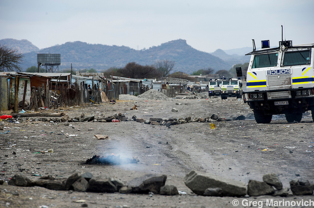 Nkaneng, Marikana, North West. South Africa. Police had running battles with residents of Nkaneng shantytown after the police disarmed about 100 miners athe day afyet Lonmon offereed striking miners a R960 increase. Burning and rock barricades were then set up in the township and police shot at, teargassed and also arrested some 14 residents. many of the injured were women.