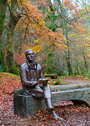 Statue of poet  Robert Burns sits on bench during autumn at the Birks O'Aberfeldy scenic area in Aberfeldy, Perthshire, Scotland,UK