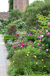 The Rose Garden at Sissinghurst Castle with Paeonia 'Felix Crousse' in the foreground