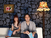 Couple sitting on sofa holding popcorn bags laughing