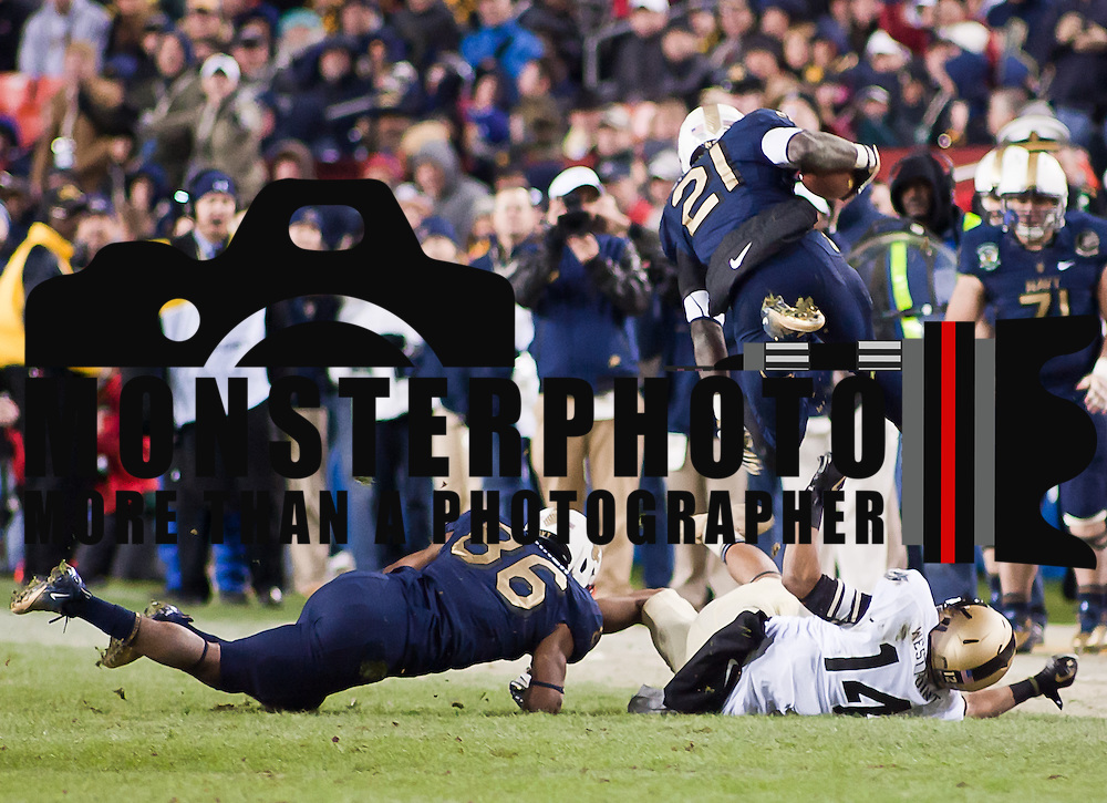 Navy Running Back Gee Gee Greene #21 hurdle over Army Cornerback Josh Jackson #14 in the 4th quarter of the 112th version of this storied rivalry between Army and Navy Saturday, Dec. 10, 2011 at Fed EX field in Landover Md. ..Navy set the tone in the fourth quarter while Army mistake cost them the game, Navy defeats Army 27-21 in front of 82,000 at Fed EX Field in Landover Md.