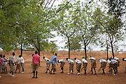 School children sweep up the playground at Pope John.s Catholic School in northern Ghana.