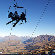 The chair lift in operation on the opening day of Coronet Peak Ski Field with the mountain ranges of the Wakatipu Basin still snowless..Unusually warm weather which included New Zealand experiencing its hottest May since record-keeping began caused long delays to the start of the ski season and the region has yet to receive a snow fall of any significance. Snow making equipment and a recent cold spell has allowed enough time for the ski field to finally open almost four weeks late.  Coronet Peak, Queenstown,  South Island, New Zealand, 30th June 2011