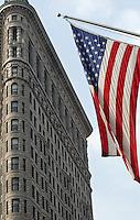 Manhattan New York 16 augustus 2003 16-08-2003 .Typische Flatiron Building op kruising broadway/ fith avenue en amirikaanse vlag in Manhattan New York City .Typical famous Flatiron Building on intersection Broadway/ fifth avenue.Flatiron Building.De Flatiron Building op Broadway, New York City.De Flatiron Building, letterlijk vertaald 'strijkijzergebouw', is een wolkenkrabber in New York City, die werd gebouwd voor het bedrijf Fuller Construction Co. Later werd de bijnaam als de officiële naam aangenomen..Het gebouw werd ontworpen door Daniel Hudson Burnham en werd voltooid in 1902. Met zijn 91 meter en 22 verdiepingen is het een van de eerste wolkenkrabbers; in zijn tijd was het het hoogste gebouw van de wereld...Detail van de gevel van de Flatiron Building.De Flatiron Building is een voorbeeld van de bouwstijl Chicago School. Zoals vele gebouwen van de Chicago School bestaat ook het Flatiron Building uit een dragende staalconstructie die bekleed met een decoratieve gevel in neorenaissancestijl..Toen het gebouw eenmaal voltooid was geloofden vele New Yorkers dat het zou instorten door de luchtstromen langs het gebouw die ontstonden door zijn scherpe driehoekige vorm. Het gebouw stortte niet in, maar er ontstond wel een ander fenomeen. Door de 'valwinden' langs de zijden van het gebouw waaiden de rokken van de vrouwen omhoog. De plaats werd berucht vanwege glurende mannen, en daarom werden er op de straten rondom het gebouw meer politieagenten ingezet..Locatie.De Flatiron Building bevindt zich in het Flatiron District, New York City, op de kruising van Broadway met Fifth Avenue...Gele taxi's worden (een beetje) groen.?.Onvermijdelijk: ook al ben je nog nooit in New York geweest, je kent de stad al. Uit de film. Van tv. Uit de krant. De gebouwen. Ground zero. Taxi's..Die 15.000 gele taxi's die op Manhattan op elk moment van de dag het overgrote deel van het verkeer uitmaken, gaan ook met hun tijd mee. Niet iedereen kan daar aan wennen..?.In 1999 verdween het vorige m
