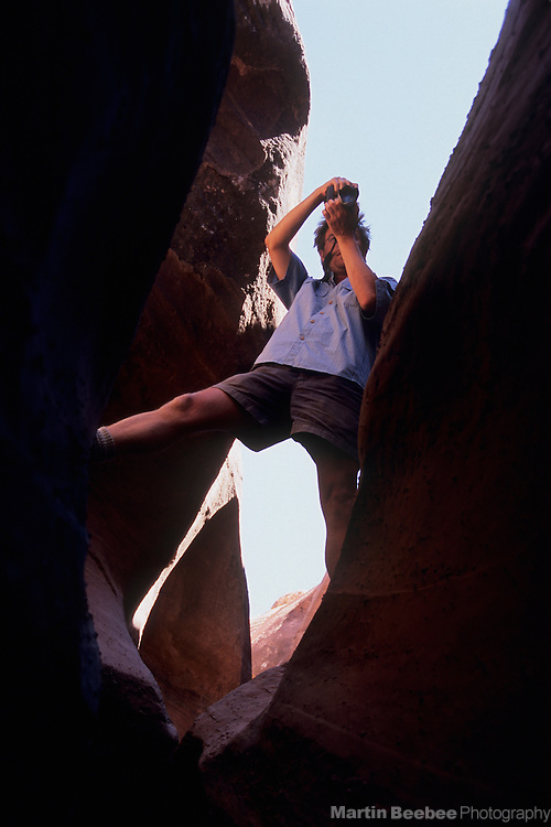 Hiker taking a picture in a slot canyon, Coyote Gulch, Grand Staircase-Escalante National Monument, Utah