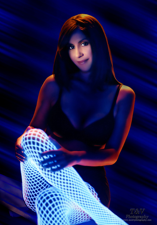Pretty woman with glowing pantyhose sitting with legs crossed.Black light