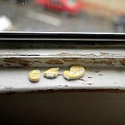 Broken birthday candles on the window ledge in the rain