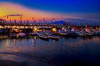 """""""Dusk on Sorrento fishing village Marina Grande""""…<br /> <br /> This is one of several sunset images of the pier and breakwater of the Marina Grande.  The bellissimo sunset illuminated the sky and water for a pleasant photograph. The second evening in Sorrento, about the time I finally learned how to drive alongside the very crazy Vespa riders who have absolutely no rules for the road, I stumbled upon Sorrento's famous Marina Grande.  Grande means big, but it's really a tiny fishing village; hardly large at all but very picturesque.  Marina Grande was a God send that evening as it supported all the qualities a tired, hungry photographer was looking for:  sunset, sea, sand, boats, skies, and great seafood.  Did I say seafood?  Arriving around 8:00 PM, just in time for dramatic sunset images, and leaving after dinner around midnight, the Marina was very Grande!  The difficulty in photographing boats in low light is the movement of the boat in the water causing """"ghosting"""" of the image.  I was fortunate to have the latest technology, a steady hand, and the hand of God keeping the boats still for my long exposures.  This image is actually technically quite miraculous.  If you look closely, the water in the foreground is blurred by its movement; however, the boats are perfectly still…very unusual.  And, yes, the seafood was """"eccezionale"""" (exceptional)!"""