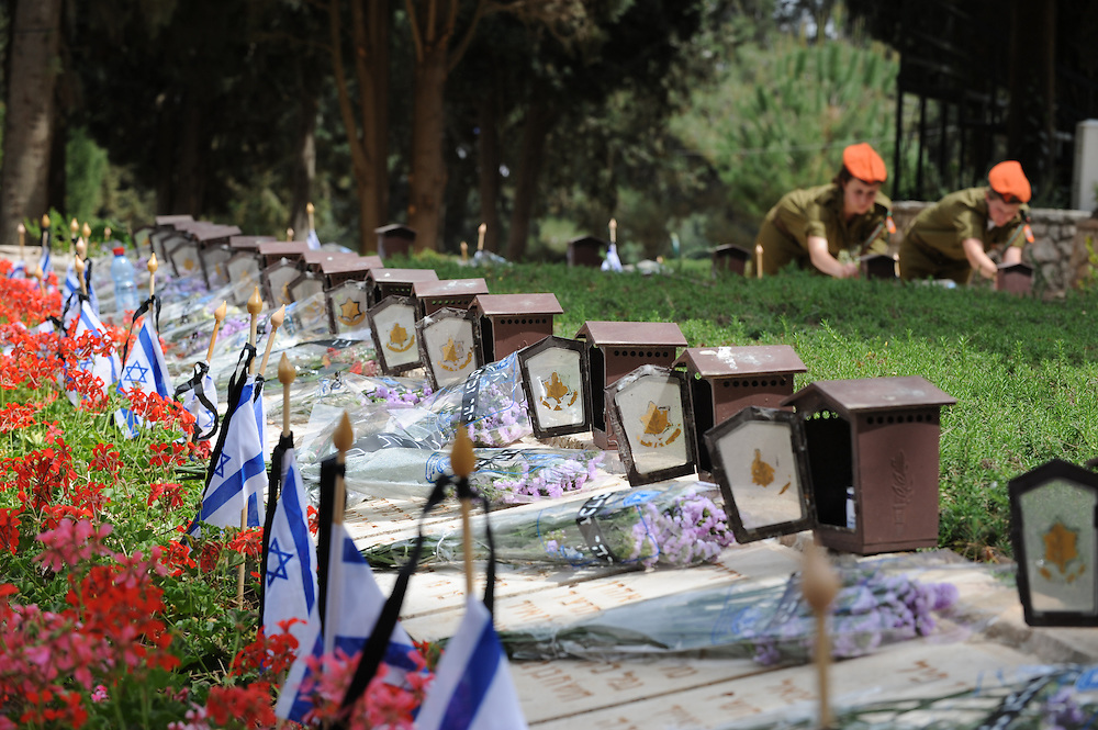 JERUSALEM, ISRAEL - APRIL 18, 2010 : Israeli soldiers light candles on graves of fallen IDF soldierss in the Military cemetery of Har Herzl (Mt. Herzl), at 18 April 2010, days before the national Memorial Day for Fallen Soldiers and Victims of Terrorism.