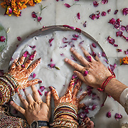 Newlyweds search for a ring in a bowl of milk and flowers as part of post-wedding ritual during a Hindu wedding in Delhi. Such customs evolved to help break the ice between the newlyweds, who in earlier times, could be meeting for the first time on the wedding day.