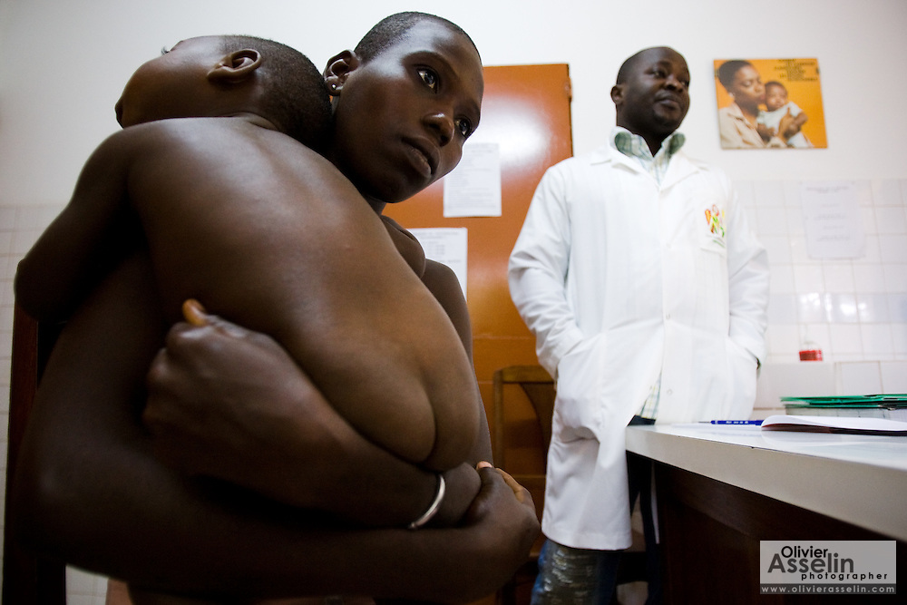 Kouadio Ahou Viviane holds her 16-month-old boy Emmanuel Ngora Kwame during a consultation with Sister Pauline Kangah Akissi (not seen) and Dr. Charles Joseph Diby (right) at the NDA health center in Dimbokro, Cote d'Ivoire on Friday June 19, 2009.