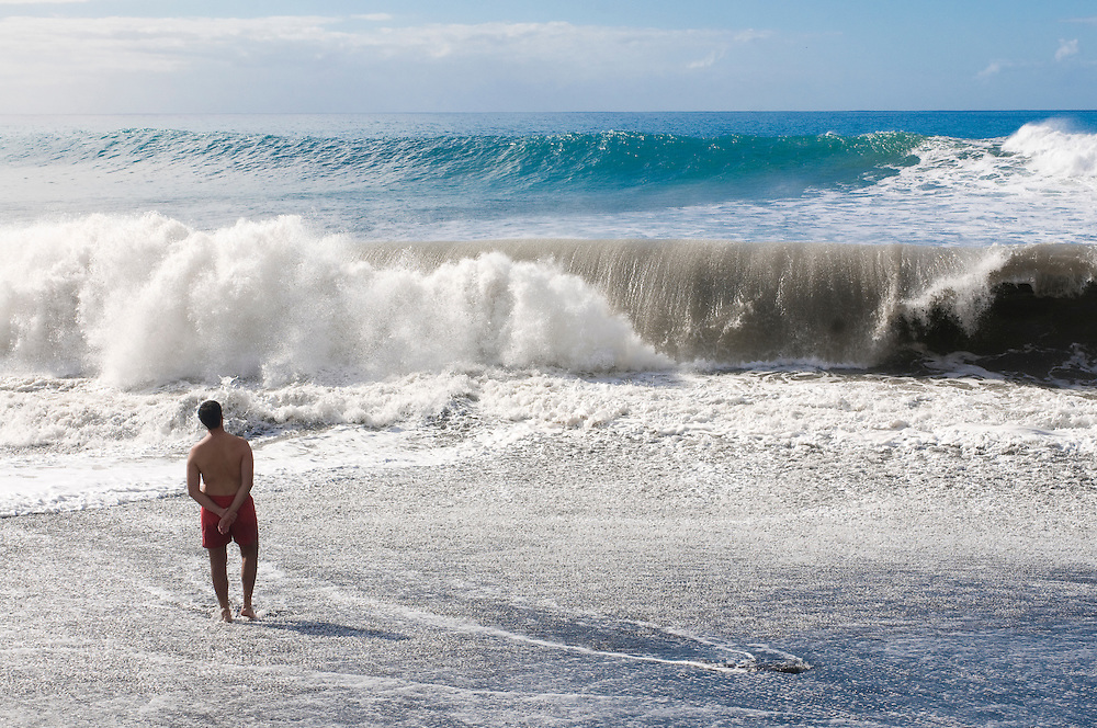 Man standing before a giant wave, La Palma, Canary islands, Spain