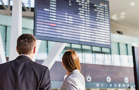 Business people looking on flight display screen in airport