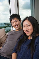 Portrait of happy Asian couple sitting on sofa at home