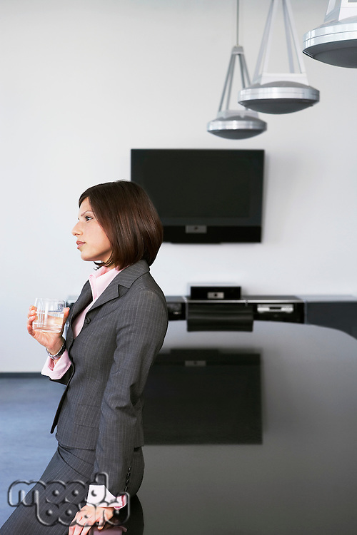Business woman with drink leaning against table in conference room