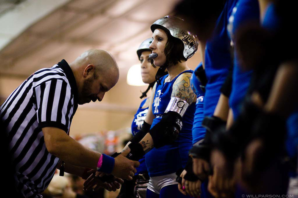 A referee checks Steely Jan of the Rollbots before their match against the Superheroes.  The San Diego Derby Dolls were at the Del Mar Fairgrounds in Del Mar, California on November 08, 2008.  The all-female roller derby league, founded in 2005, features serious competition among skaters with tongue-in-cheek names such as Anita Battle and Isabelle Ringer.
