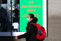 © Licensed to London News Pictures. 16/03/2020. London, UK. A woman wearing a face mask on Oxford Street walks past a St Patrick's Day poster, amid an increased number of Coronavirus (COVID-19) cases in the UK. 35 coronavirus victims have died and 1,372 have tested positive forthe virusin the UK as of9amon Sunday, 15 March 2020. Photo credit: Dinendra Haria/LNP