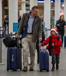 © Licensed to London News Pictures. 20/12/2019. Hogan Frank 11 and his dad arriving for their train to Disneyland Paris as the Christmas Getaway starts at St Pancras Station. Heavy rain today is causing chaos for the  thousands who are expected to travel for the festive period: Alex Lentati/LNP