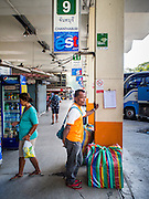 04 JANUARY 2015 - BANGKOK, THAILAND:  A passenger waits for a Chanthaburi bound bus at the Ekkamai Bus Station in central Bangkok. Buses from Ekkamai go to Chonburi, Rayong, and Trat provinces, including the resort city of Pattaya. Millions of Thais hit the road Sunday returning to Bangkok after the long weekend New Year holiday. Train stations and trains were packed and the state owned bus company scheduled thousands of extra buses to handle the demand.   PHOTO BY JACK KURTZ