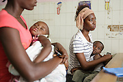 Another mother (left) waits with her child while Kadidiatou Sy, 27, and her son Junior Karampire, 5, who suffers from recurring ear infections, meet with a doctor at the Koumassi General Hospital in Abidjan, Cote d'Ivoire on Friday July 19, 2013.
