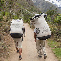 Peru, Piscacucho, Porters carrying hikers' supplies walking along Inca Trail to Machu Picchu along Urubamba River