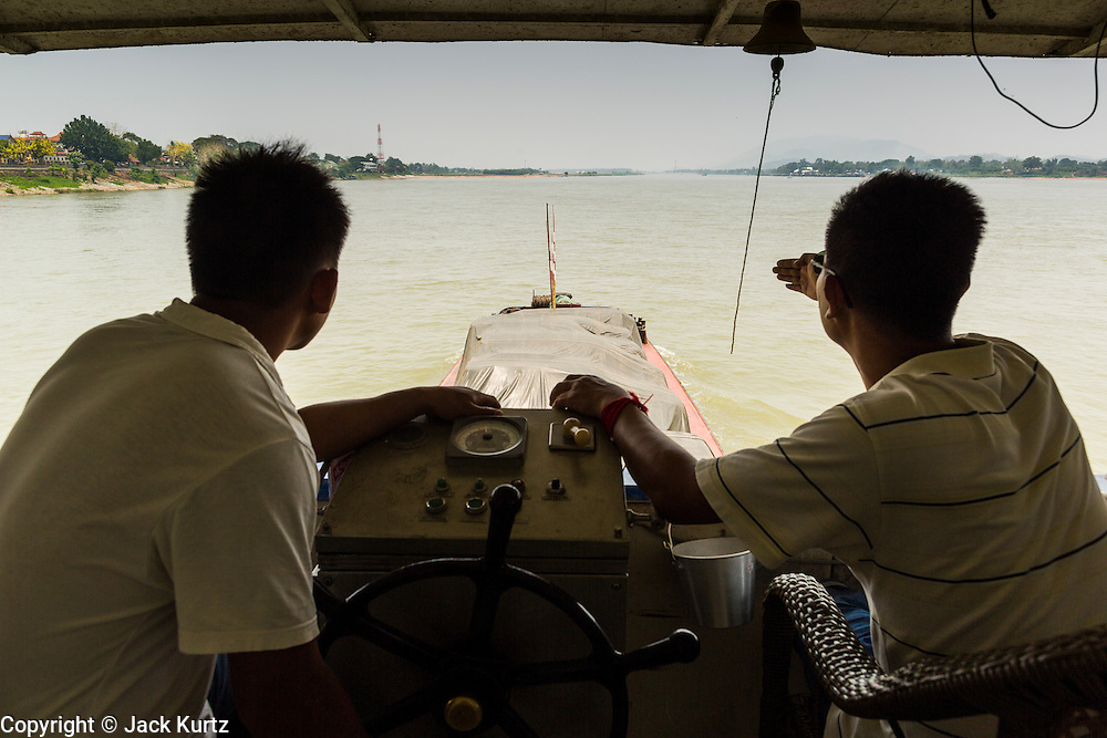 24 APRIL 2014 - CHIANG SAEN, CHIANG RAI, THAILAND:  The captain (right) and first mate on a Chinese cargo steer the boat up the Mekong River. The boat was carrying a cargo of cars, Red Bull energy drink and passengers and was bound for Kunming in China. Chinese businesses play an increasingly important role in the Chiang Rai economy. Consumer goods made in China are shipped to Thailand while agricultural products made in Thailand are shipped to China. Large Chinese cargo boats ply the Mekong River as far south as Chiang Saen in the dry season and Chiang Khong when river levels go up in the rainy season.    PHOTO BY JACK KURTZ