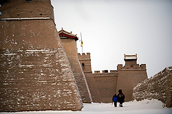A staff member and a camel walk in the Jiayu Pass scenic spot after snowfall in Jiayuguan City, northwest China's Gansu Province, December 21, 2012. Photo by Imago / i-Images...UK ONLY