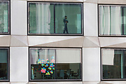 An employee and Post-it notes stuck to the window of a meeting room in an office on London Wall in the City of London - the capital's financial district, on 21st August 2018, in London, England.