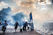 01 DECEMBER 2013 - BANGKOK, THAILAND: Thai anti-government protestors run past one of their own barricades and through a cloud of tear gas in Bangkok. Thousands of anti-government Thais confronted riot police at Phanitchayakan Intersection, where Rama V and Phitsanoluk Roads intersect, next to Government House (the office of the Prime Minister). Protestors threw rocks, cherry bombs, small explosives and Molotov cocktails at police who responded with waves of tear gas and chemical dispersal weapons. At least four people were killed at a university in suburban Bangkok when gangs of pro-government and anti-government demonstrators clashed. This is the most serious political violence in Thailand since 2010.    PHOTO BY JACK KURTZ