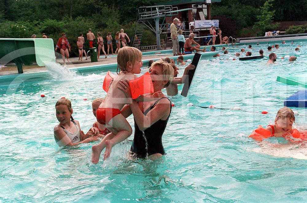 balkbrug : zwemvierdaagse buiten de banen was er gelegenheid tot spelen  wat deze moeder dan ook met beide handen aangreep..foto frank uijlenbroek©1996/nico