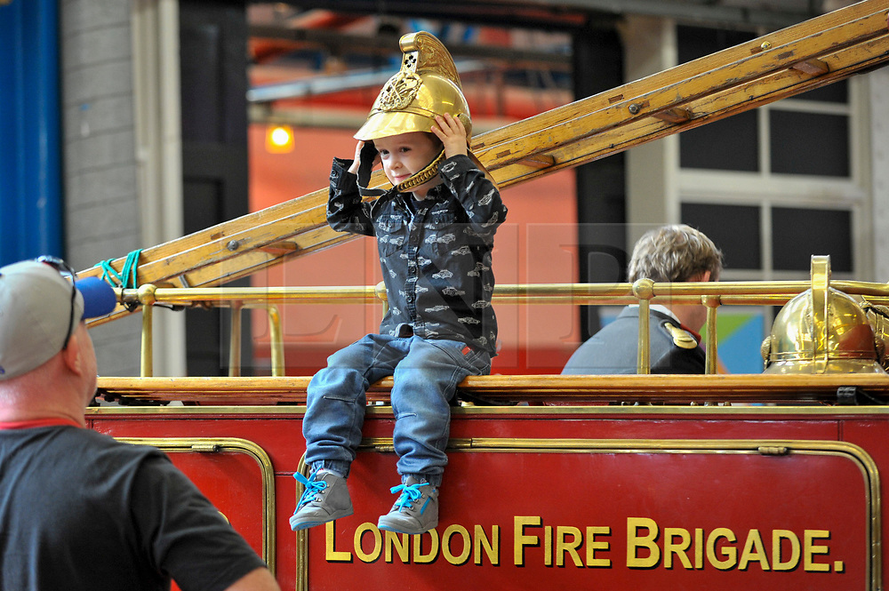 © Licensed to London News Pictures. 09/09/2017. London, UK. A young visitor tries on a helmet atop a Dennis N-Type 1916 fire engine at London Fire Brigade's annual Fire Engine Festival in Lambeth.  The earliest motorised fire engines still working, London Fire Brigade's brand new pump as well as firefighter uniforms are on display. Photo credit : Stephen Chung/LNP