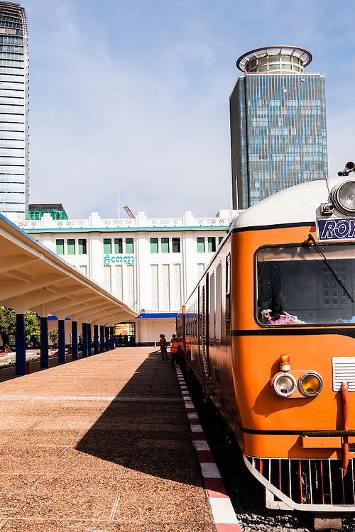 Monk boarding Orange Line train at main train station in Phnom Penh. The station was built in 1932 from reinforced concrete[2] to service the railway to Battambang.