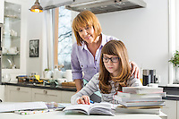 Mother assisting daughter in doing homework in kitchen