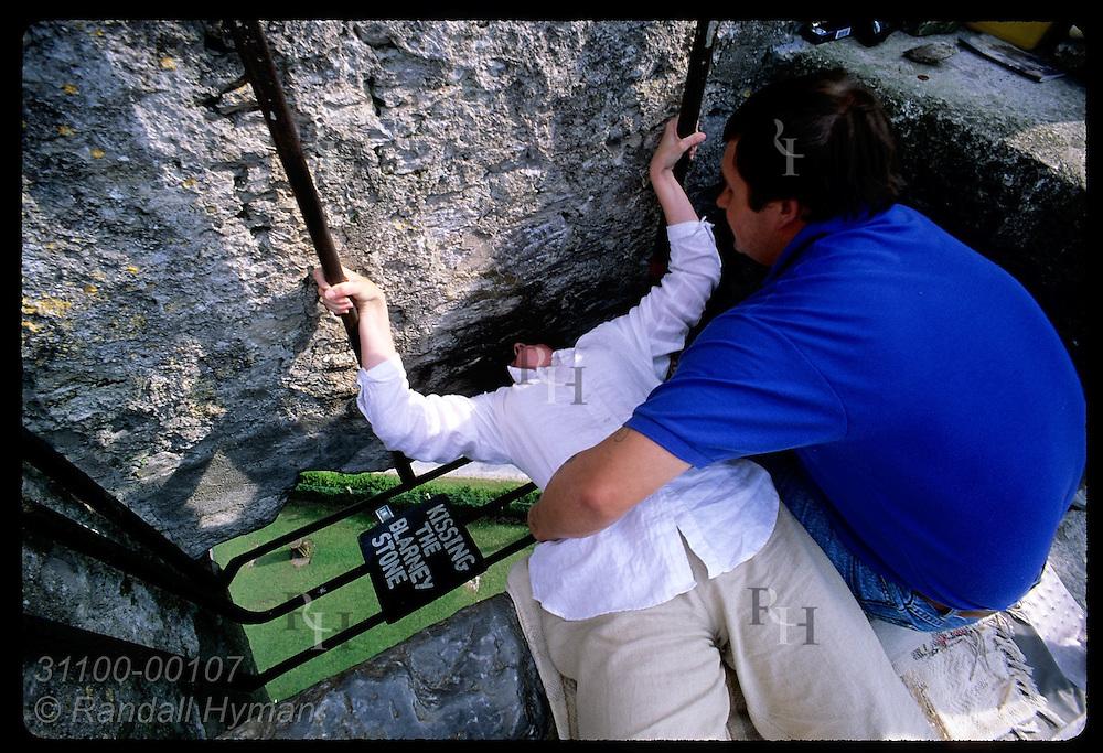 'Holder' Nigel Barrows helps woman lean back to kiss Blarney Stone atop 130' Blarney Castle. Ireland