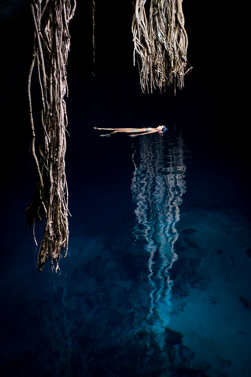 Sara floating in Cenote.  Illusion of tree vine reflection holding her on waters surface.<br />