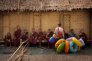 An inflatable toy seller offering his wares next to a group of monks. Shwet Set Taw, Magwai<br /> Division, Myanmar. February 2014.